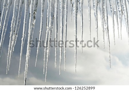 Beautiful icicles closeup on a background of clouds
