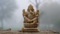 Beautiful Idol of Ganesha in Yoga action. God Ganesha statue and behind white mist background.