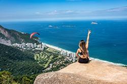 Beautiful image from above of Pedra Bonita overlooking the neighborhood of São Conrado with girl contemplating a beautiful blue sky, sea, nature with a hang glider over the sky of Rio de Janeiro Brazi
