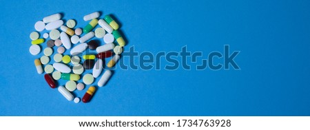 Photo of Beautiful image of a heart made of multi-colored pills and capsules on a blue background. Love in the form of a heart. web banner on the site with a free zone for text on the left side. Isolated.