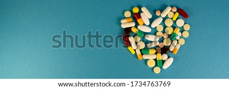 Photo of Beautiful image of a heart made of multi-colored pills and capsules on a greenish background. Love in the form of a heart. web banner on the site with a free zone for text on the left side. Isolated.