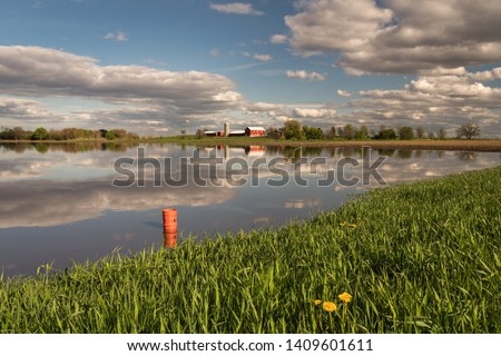 Beautiful image of flooded farm field with clouds & farm reflected in standing water. Historic rains flooded fields & prevent farmers from planting crops. Concepts of crop insurance, natural disaster