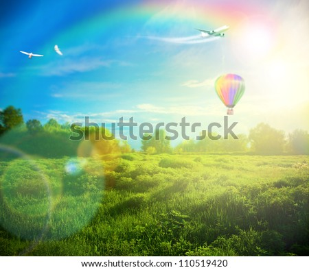 Beautiful image of stunning sunset with atmospheric clouds and sky over vibrant fields in  countryside landscape with hot air balloon, birds and airplane flying high