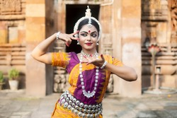 Beautiful Indian classical Odissi dancer Posing at Lingaraja Temple.Odissi or Orissi dance is a major ancient Indian classical dance form originated in the Hindu temples of Odisha.