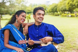 Beautiful indian couple in ethnic clothes playing guitar in a park and singing