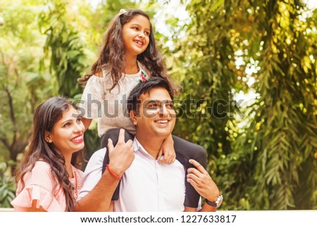 Beautiful Indian family enjoying in a park. Little girl sitting on her father's shoulders. #1227633817
