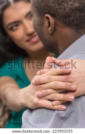 beautiful indian girl hugging her boyfriend. back view of black man looking at indian girl