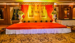 Beautiful Indian wedding ceremony stage set in colors and entrance in red and floral patterns