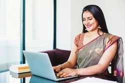Beautiful Indian woman in a saree working on her laptop from home office
