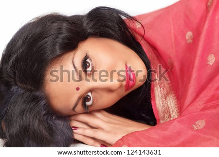 Beautiful Indian woman in sari resting head on hands