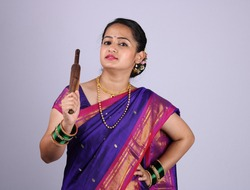 Beautiful Indian woman or girl holding rolling pin in hand. This is front facing photo in which she is wearing Indian ethnic wear this is saree.