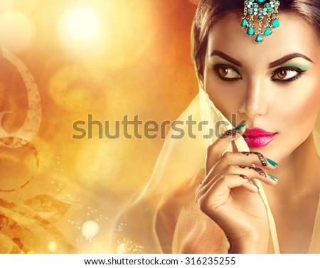 Beautiful Indian woman portrait. Hindu girl with menhdi, perfect make-up and accessories hiding her face behind a veil. Indian marriage. Traditions and culture concept