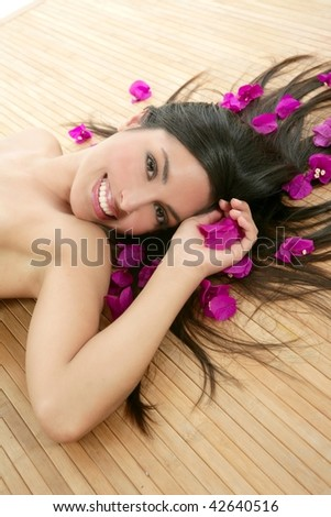 Beautiful indian woman portrait in a beauty spa with bougainvillea flowers