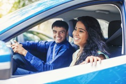 Beautiful Indian woman riding in a blue car with a driver