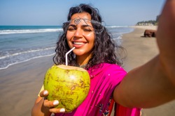 beautiful indian woman taking a portrait selfie photo on the camera phone in pink stylish sari ,toothy white smile sun summer by sea goa. healthy eating concept Indian Ocean bay