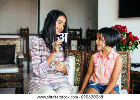 Beautiful Indian woman  teaching her daughter to recognize Hindi language alphabets