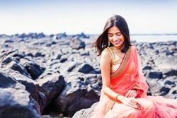 Beautiful indian woman wearing saree sitting on a shore in Mumbai