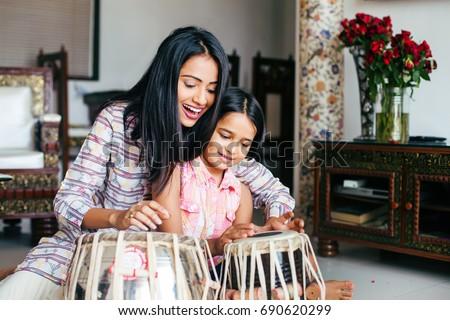 Beautiful Indian woman wearing traditional kurta teaching her daughter to play Tabla