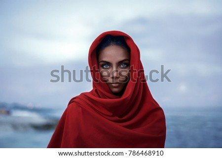 Stock Photo Beautiful indian woman with red paranja and blue eyes in the twilight