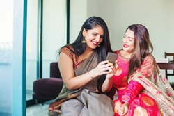 Beautiful Indian women in saree and ethnic dress using mobile phone at home