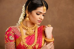 Beautiful Indian young Hindu Bride against brown background in studio shot