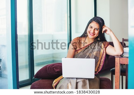 Beautiful Indian young woman in a saree using her laptop, working from home Zdjęcia stock ©