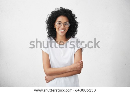 Beautiful inexperienced fledgling young dark-skinned female singer standing at white studio wall with arms folded, smiling shyly and feeling a bit uncomfortable during audition to musical show