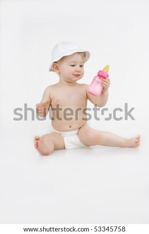 Beautiful infant in white hat examines bottle milks on white background.