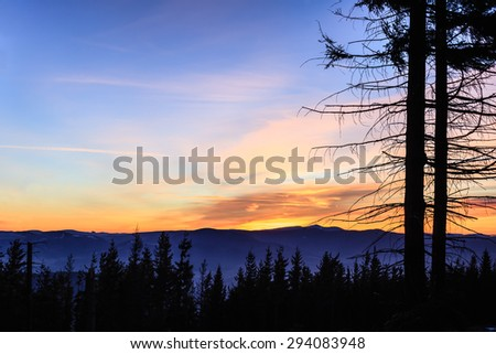 Beautiful inspirational landscape sunset in mountains. Winter hiking trail at night with colorful sunset sky.
