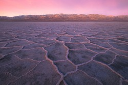 Beautiful, inspiring landscape and halite texture of Badwater Basin salt flats under a colourful, vibrant sunset or sunrise pink sky at Death Valley National Park, USA.