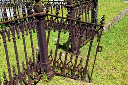 Beautiful iron gate hangs from its broken hinges.  It is attached to a decorative iron fence surrounding a grave.  It is in disrepair.