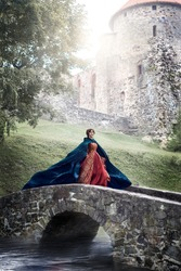 Beautiful Isabella of France, queen of England on Middle Ages period in red gown near medieval castle