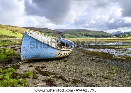 Beautiful Isle of Skye Scotland landscape. Old abandoned wooden boat wreck with peeling blue paint on the shore at Loch Harport at low tide