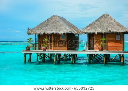 Photo of beautiful isolated luxury water bungalows Maldives in the blue green ocean of the maldives