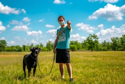 Beautiful Italian man walking his black dog in a sunny summer day. Outdoor sport activity alone and with surgical mask due to covid-19, new coronavirus, restrictions.