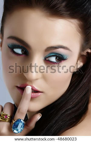 beautiful Italian model pressing finger on her lips in secret sign, with turquoise and pink make-up.