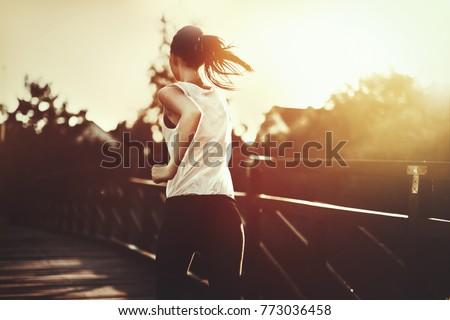 Beautiful jogger crossing bridge #773036458