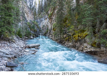 Beautiful Johnston Canyon walkway with turquoise water below, in Banff National Park, Alberta, Canada.  Shot with long exposure to give colorful river a smooth & dreamy effect. #287510693