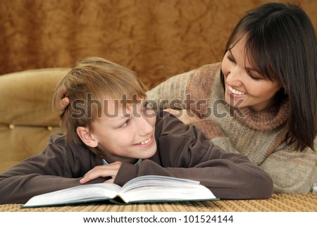 Beautiful joy Caucasian mother with her son reading a book on a brown background
