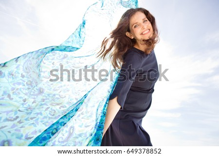 Beautiful joyful mature woman smiling looking, holding fabric in the breeze, floating against blue sunny sky, carefree outdoors. Healthy well being recreation lifestyle, plain nature background space.