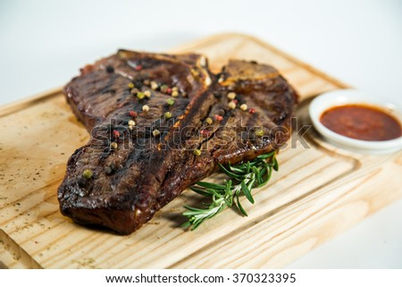 Beautiful juicy well done steak with sauce on a wooden Board #370323395