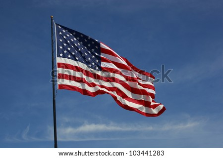 Beautiful jumbo American flag on a flag pole flying against a blue sky