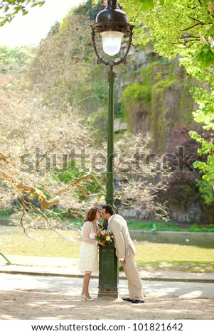 Beautiful just married couple kissing by lantern