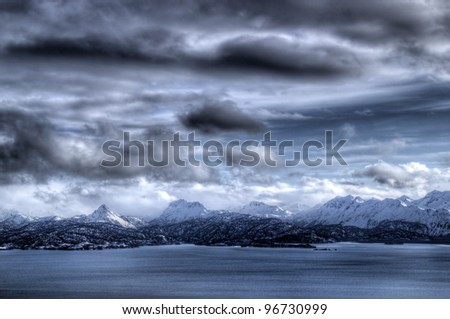 Beautiful Kenai mountains in Alaska with the Kachemak bay with storm clouds in winter.