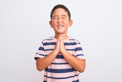 Beautiful kid boy wearing casual striped t-shirt standing over isolated white background begging and praying with hands together with hope expression on face very emotional and worried. Asking