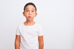 Beautiful kid boy wearing casual t-shirt standing over isolated white background puffing cheeks with funny face. Mouth inflated with air, crazy expression.