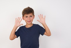 Beautiful kid boy wearing casual t-shirt standing over isolated white background showing and pointing up with fingers number ten while smiling confident and happy.