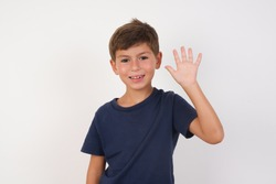 Beautiful kid boy wearing casual t-shirt standing over isolated white background Waiving saying hello happy and smiling, friendly welcome gesture.