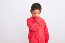 Beautiful kid boy wearing elegant red shirt standing over isolated white background tired rubbing nose and eyes feeling fatigue and headache. Stress and frustration concept.
