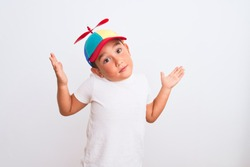 Beautiful kid boy wearing fanny colorful cap with propeller over isolated white background clueless and confused expression with arms and hands raised. Doubt concept.